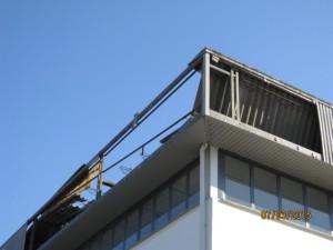 una porzione laterale del tetto danneggiato nella copertura in cemento/amianto.